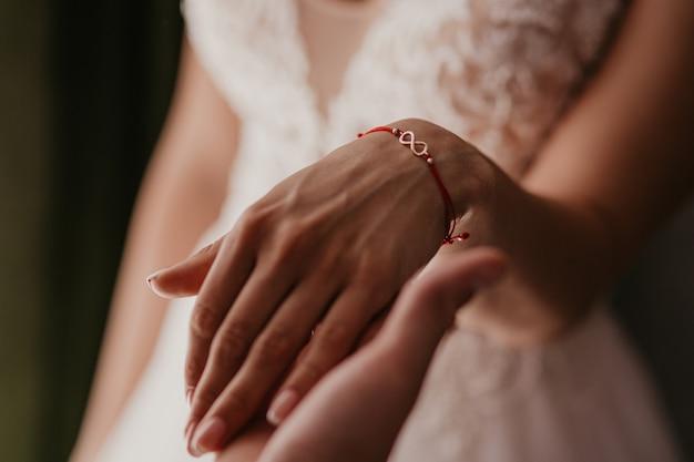 Een hand van een bruidspaar raakt elkaar aan. handen jonggehuwden met trouwringen close-up
