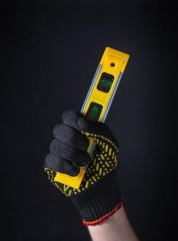 Een hand van een vakman in handschoen heeft een constructieniveau van gele kleur op een donkere achtergrond