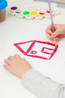 Een hand van meisje met penseel tekening huis van droom door aquarel op wit vel papier. kind tekent huis.