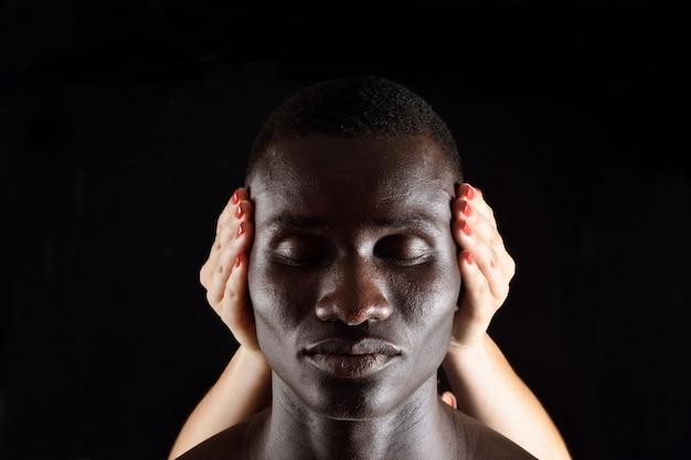 Een hand voor een oren van de afrikaanse man op zwart