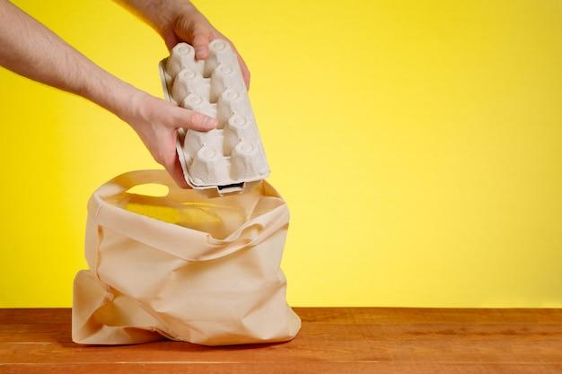 Een hand zet cassette met eieren in een boodschappentas