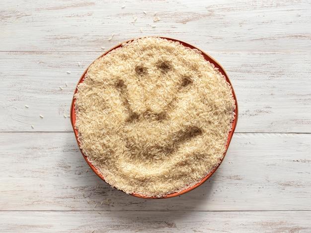 Een handafdruk in een bord rauwe rijst. bovenaanzicht.