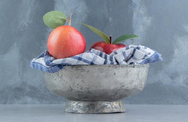 Een handdoek en appels in een metalen kom op marmer.