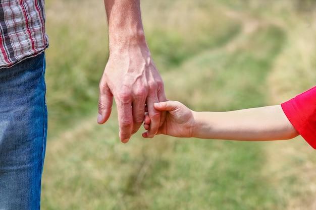 Een handen van gelukkig kind en ouder op de natuur in het parkfamilieconcept