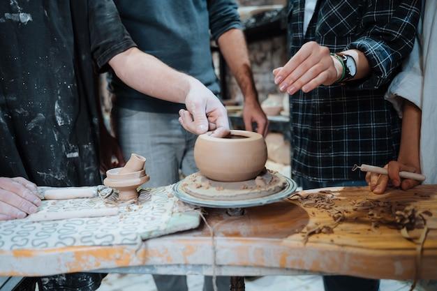 Een handgemaakte aarden pot maken. aardewerkles met meester.