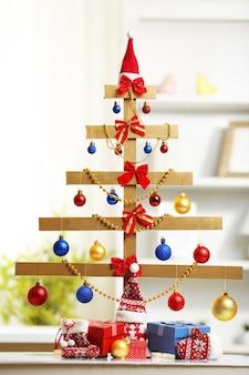 Een handgemaakte kerstboom en cadeautjes op tafel, in de kamer