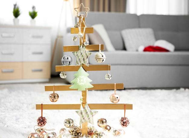 Een handgemaakte kerstboom en kerstballen op de vloer in de kamer