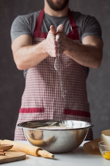 Een handvol bloem met ei op een rustieke keuken. kneed het deeg tegen de tafel van mannenhanden
