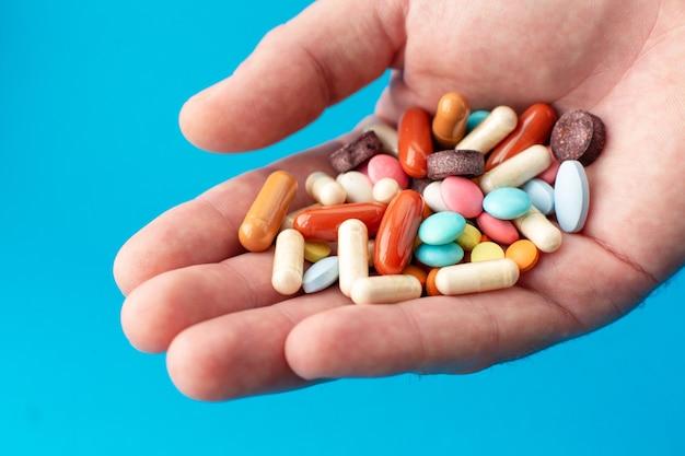 Een handvol gekleurde pillen op de handpalm. medisch concept.