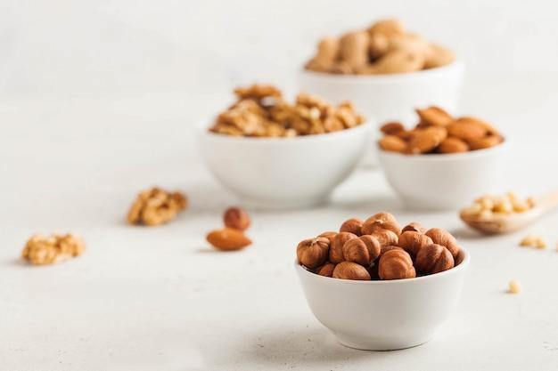 Een handvol hazelnoten in een witte kom, diverse noten op een lichte achtergrond. gezonde tussendoortjes, gezonde vetten. kopieer ruimte.