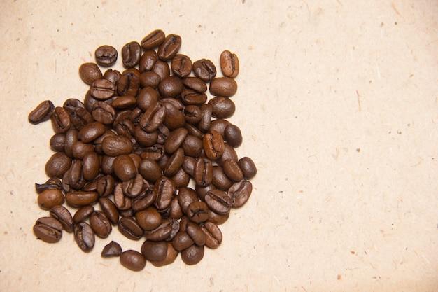 Een handvol koffiebonen op een beige achtergrond. inpakpapier.