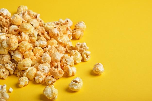 Een handvol popcorn op een gele achtergrond