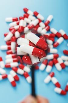Een handvol rode en witte pilcapsules wordt onderzocht met een vergrootglas op een blauwe achtergrond. detailopname. bovenaanzicht