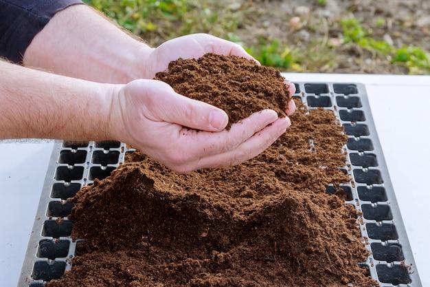 Een handvol vruchtbare grond in handen van de boer.