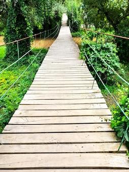 Een hangende houten voetgangersbrug over de rivier, midden in een groen bos.