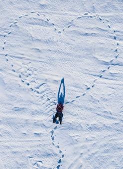 Een hart dat in de winter is getekend in een veld in de sneeuw dat van boven is genomen door een drone. valentijnsdag.