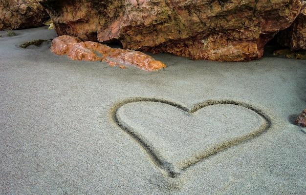 Een hart getekend op het zand van het ongerepte strand: een gebaar van zoete en poëtische liefde voor degenen die echt liefhebben