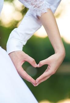 Een hart uit de handen die de bruidegom en de bruid maakten
