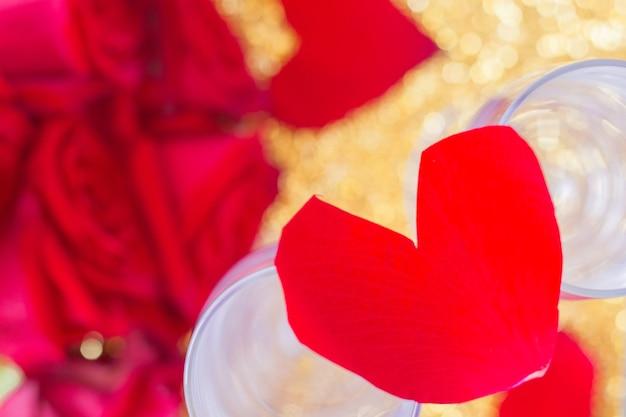 Een hart van rozenblaadjes ligt op twee glazen met onderaan een wazig boeket rode rozen en ...