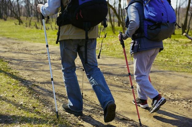 Een hart voor twee zwervers. leeftijd familie paar man en vrouw in toeristische outfit wandelen op groen gazon in de buurt van bomen in zonnige dag. concept van toerisme, gezonde levensstijl, ontspanning en saamhorigheid.