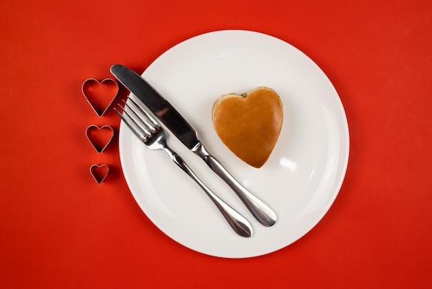 Een hartvormige hamburger op een witte plaat met een mes en vork op een rode achtergrond
