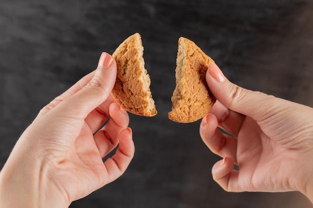 Een havermoutkoekje in de hand in twee stukken snijden.