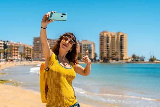Een heel gelukkige jonge vrouw die een selfie met de telefoon neemt in playa del cura in de kustplaats torrevieja, alicante, valenciaanse gemeenschap