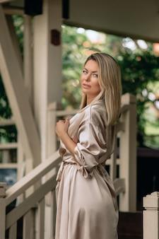 Een heel mooie blonde vrouw in een zijden lange badjas poseert 's ochtends op het terras