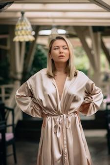 Een heel mooie blondine in een zijden lange badjas poseert 's ochtends op het terras