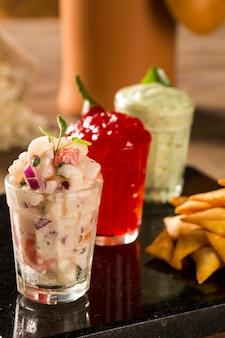 Een heerlijk kopje guacamole, hete pepergelei, naast verse ingrediënten op een tafel met tortillachips en salsa
