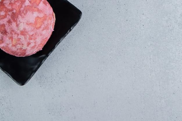 Een heerlijk roze koekje op een zwarte schotel op marmeren achtergrond.