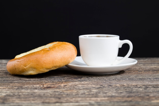 Een heerlijk vers broodje en een kopje zwarte aromatische koffie, vers gezette zwarte koffie en een klein dessert liggen samen, eten in de cateringservice
