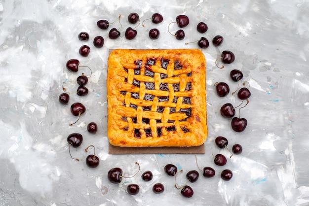 Een heerlijke aardbeientaart van bovenaf met aardbeiengelei erin, samen met verse kersen op de grijze bureaucake