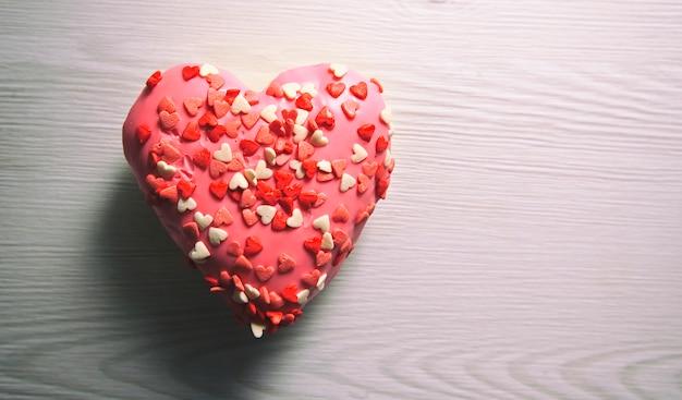 Een heerlijke donut in vorm van hart op houten tafel