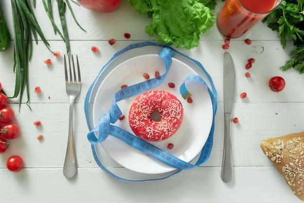 Een heerlijke donut ligt op een bord en eet om te eten. problemen met goede voeding en het concept om te kiezen tussen gezond en niet gezond voedsel