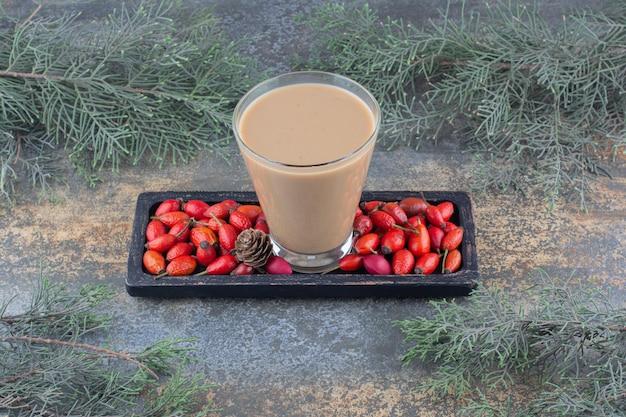 Een heerlijke kop koffie met rozenbottels op donker bord. hoge kwaliteit foto
