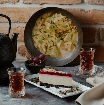 Een heerlijke plak new york-cheesecake met aardbeienjam bovenop en chicolate crêpes op de basis