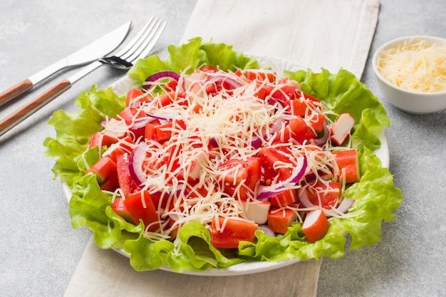 Een heerlijke salade van krabsticks cherrytomaatjes en geraspte kaas met uien in een serveerschaal.