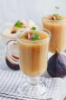 Een heerlijke verse meloen en vijgen smoothie in een glas met een schijfje vijg op de witte houten achtergrond. gezond voedselconcept.