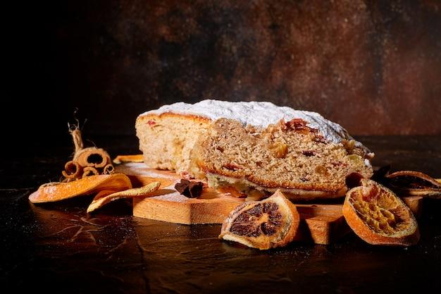 Een heerlijke zoete cake bestrooid met poedersuiker ligt omringd door gedroogde sinaasappels en kaneel en een houten plank