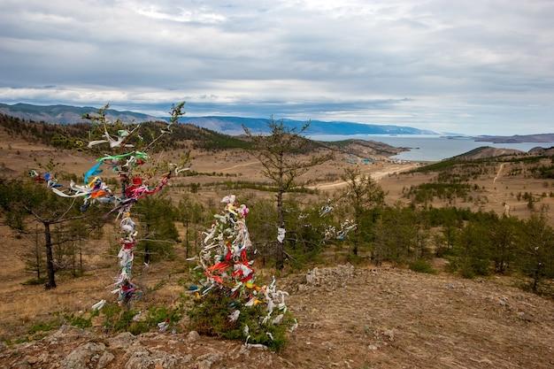 Een heilige plaats van macht met linten aan het baikalmeer op een heuvel. tradities van boerjatië in rusland. sjamanisme van het eiland olkhon.