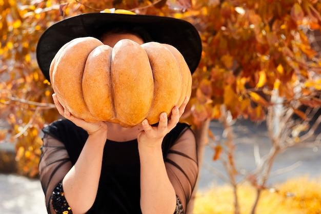 Een heks die haar gezicht bedekt met oranje pompoen.
