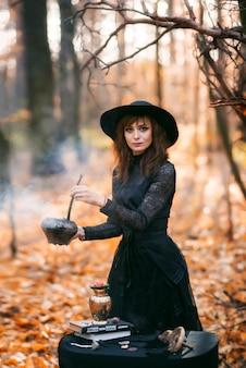 Een heks in het herfstbos. een vrouw in een zwarte lange jurk die een drankje kookt, bereidt zich voor op halloween