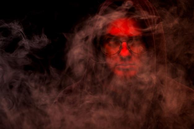 Een heksenmeester met een rood gezicht in een kap en een bril op een zwarte achtergrond in rook.