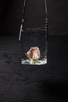Een helder ijsblokje met een bevroren rozenbloem erin in een barman ijstang, donkere achtergrond
