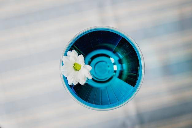 Een helderblauwe cocktail in een nick & nora glas gegarneerd met een kamillebloem