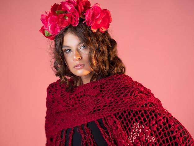 Een heldere en gedurfde jonge vrouw met rozen op haar hoofd en een rode gebreide cape. modebeeld met etnische motieven, portret van een mooie brunette op roze