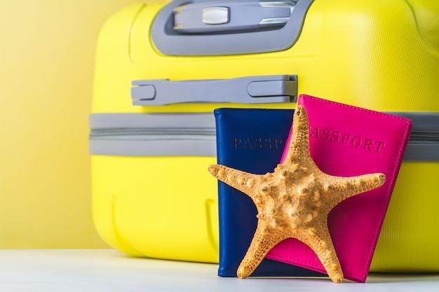Een heldere, gele reiskoffer, paspoort en zeester. reizen concept.