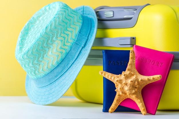 Een heldere, gele reiskoffer, paspoorten, blauwe hoed en schelpen. reizen concept. vrije tijd, vakantie