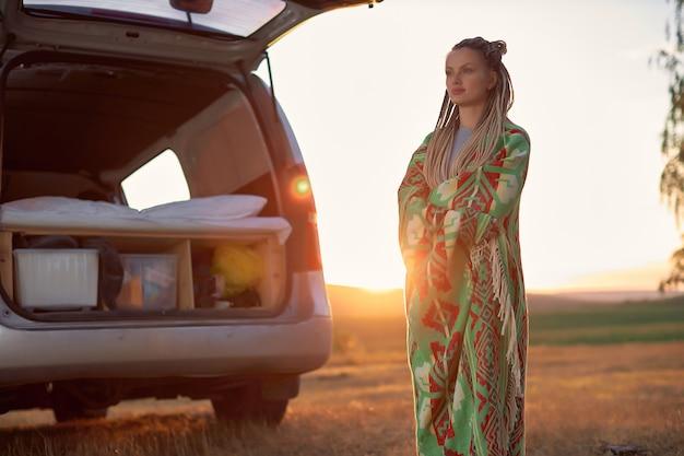 Een heldere jonge vrouw staat in een veld bij zonsondergang in de buurt van haar auto en kijkt in de verte van hoge kwaliteit.